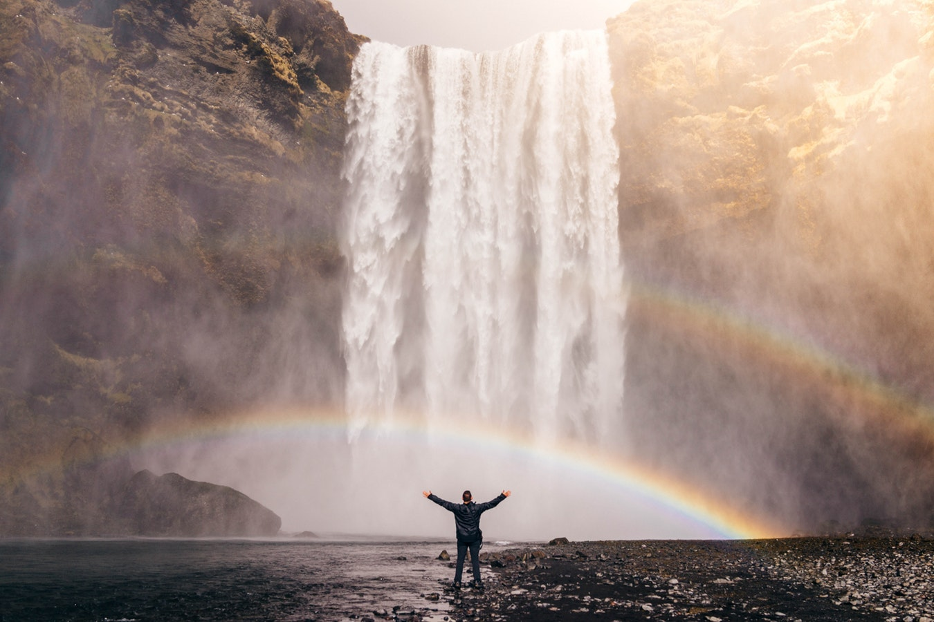 person with outstretched arms in front of a huge waterfall with a rainbow in front of hime