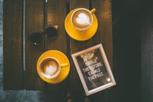 two yellow coffee mugs with a pair of sunglasses on a table with a framed photo by toa heftiba