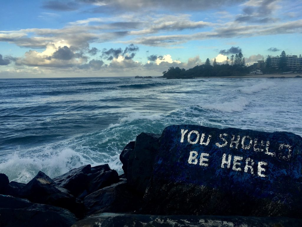 land divided by an ocean with a painted rock that says 'you should be here.'