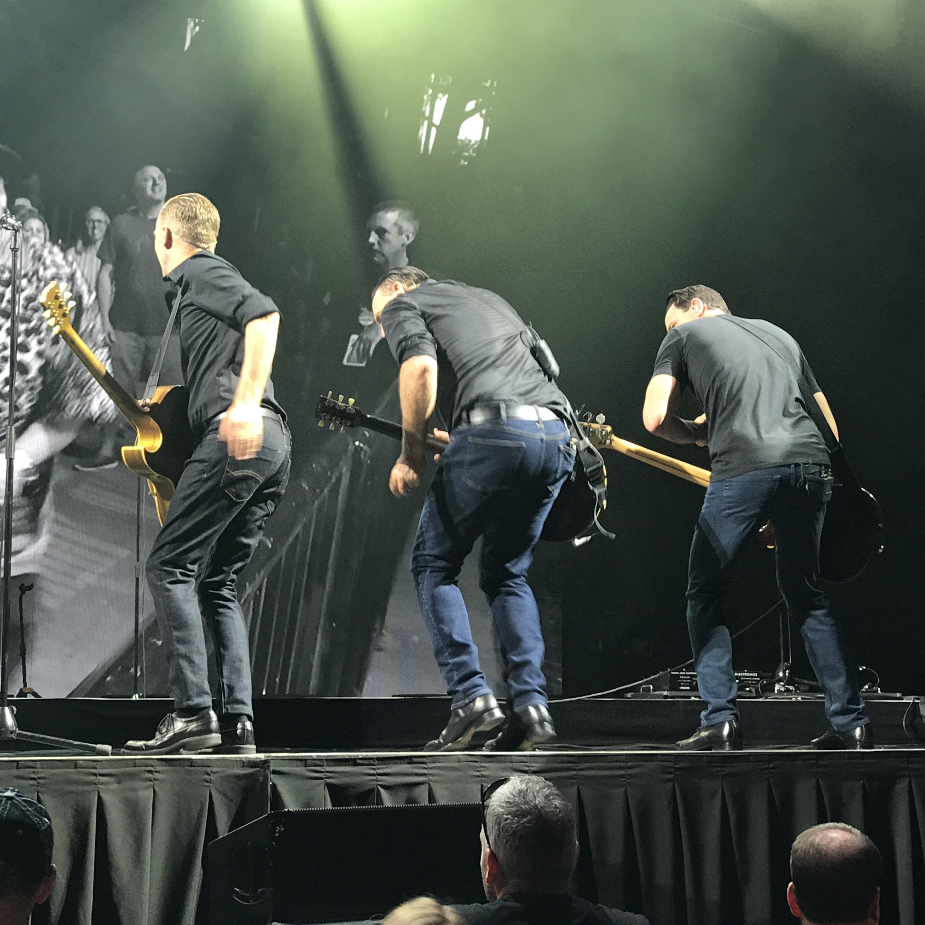 Bryan Adams with his guitarists, shaking their backsides on stage