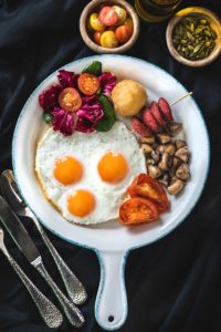 three sunny-side up eggs with salad, berries, mushrooms, and tomato wedges on white plate with handle