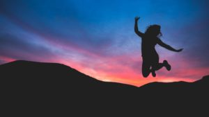 lady jumping at dusk with mountains in the background