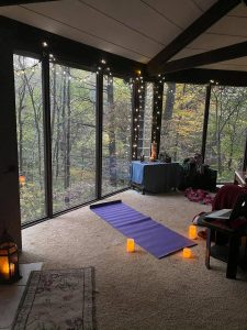 yoga matt with candles overlooking a forest