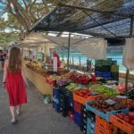 lady in red summer dress and sandals walks along the aisles of a farmers market