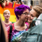 two humans being close, one wearing a rainbow tie-dyed shirt with purple hair and glasses at a Pride event